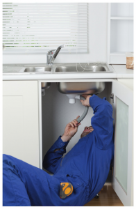 Plumber working under sink