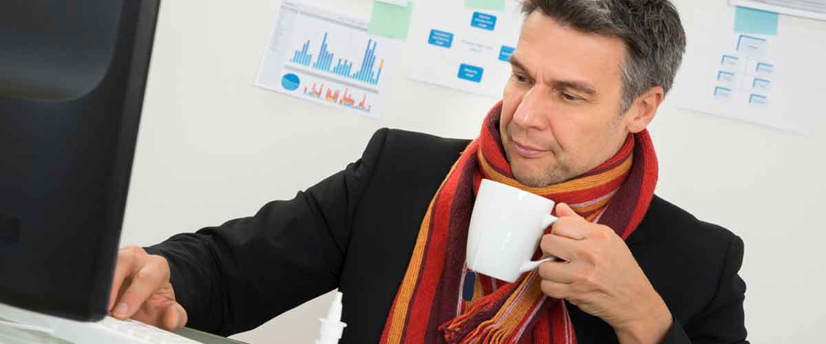 Businessman wearing scarf in office, with hot drink