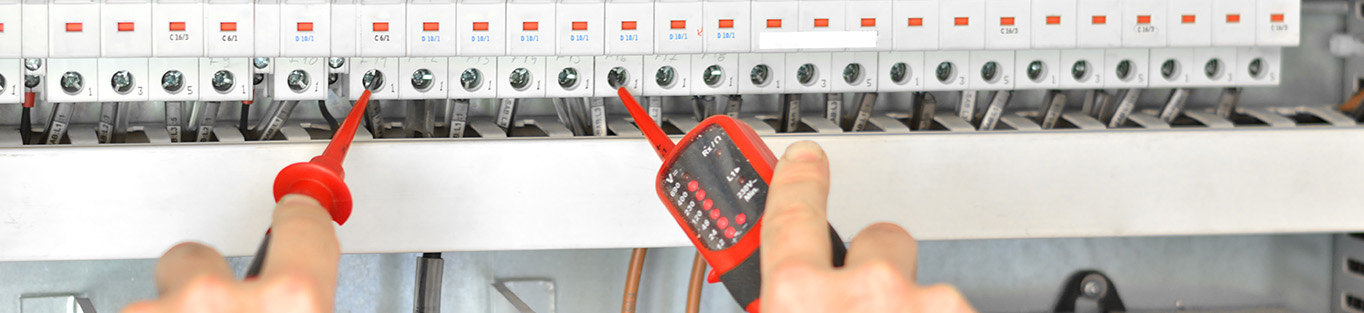 Hands of technician examining fusebox with multimeter probe