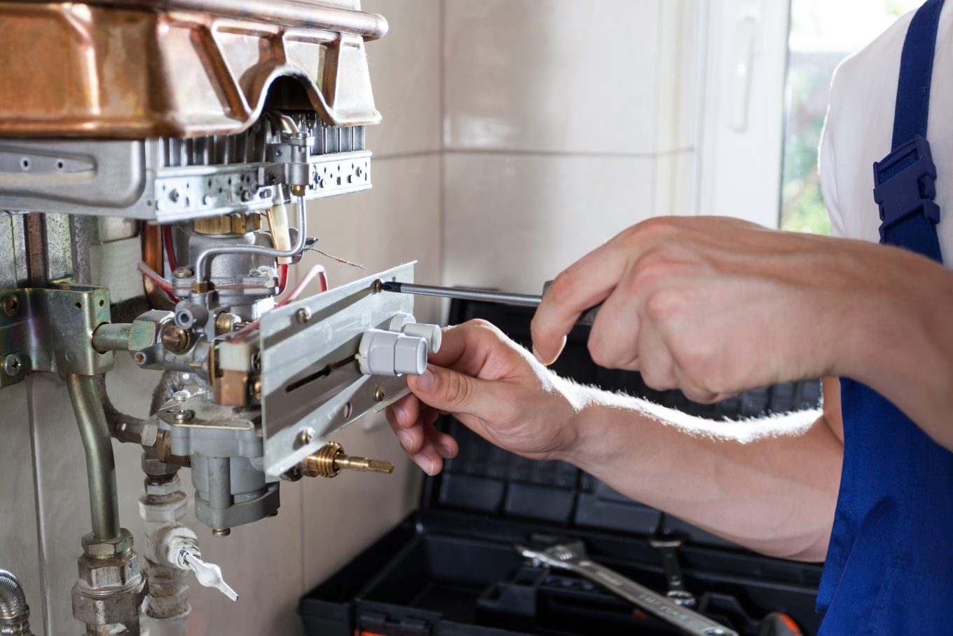 Repairman fixing a gas water heater with a screwdriver