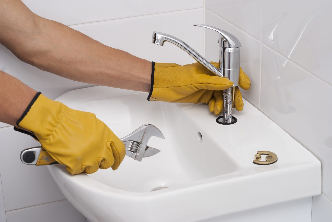 plumber installs a new faucet for a sink
